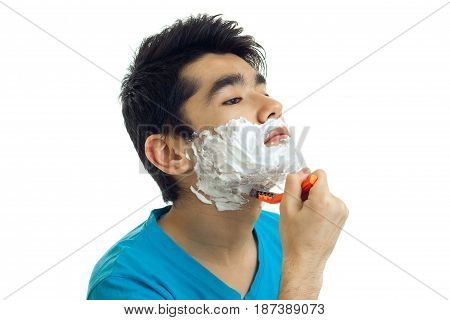 handsome young guy with black hair stands sideways with foam on your face and shaves his beard machine close-up