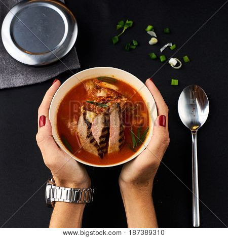 Korean cuisine. Spicy kimchi soup served in a bowl standing on black background. Woman hands holding bowl.