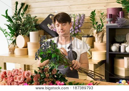 Flowers delivery shop. Male florist making rose bouquet. Man assistant or owner in floral design studio, making decorations and arrangements. Creating order