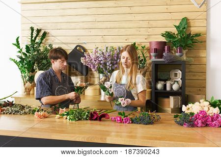 Small business. Flowers delivery. Florists creating order, making rose bouquet in flower shop.