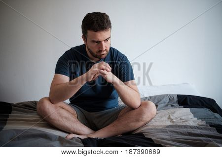 Depressed Man Seated On His Bed Feeling Bad