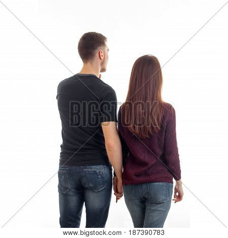 a young couple standing with back to the camera and are coming forward isolated on white background