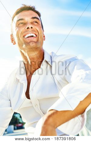 Happy and handsome man smiling, joyful smile outdoor. A joyous and beautiful man with perfect teeth. Blue sky behind.