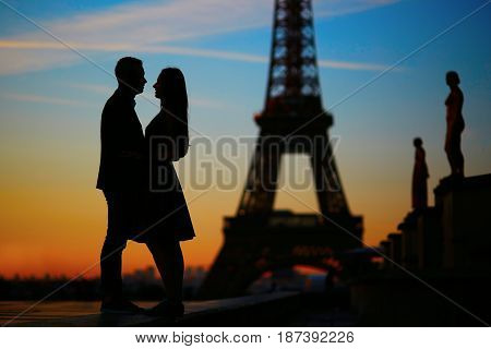 Silhouettes Of Romantic Couple Near The Eiffel Tower At Sunrise