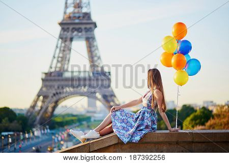 Girl With Colorful Balloons Near The Eiffel Tower In Paris, France