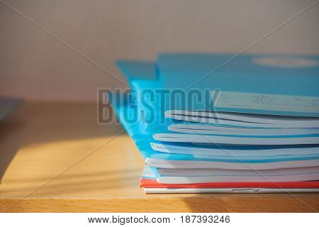 Stack of blue notebooks on wooden table with sunlight.