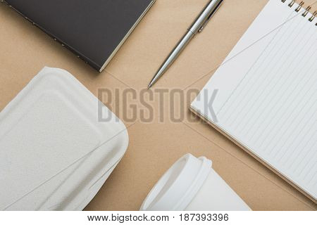 Notebooks pen takeaway coffee cup and food box on brown paper - flat lay (top view)