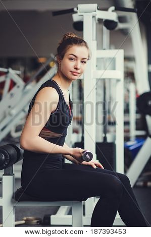 Beautiful sports girl picks up dumbbells in the gym