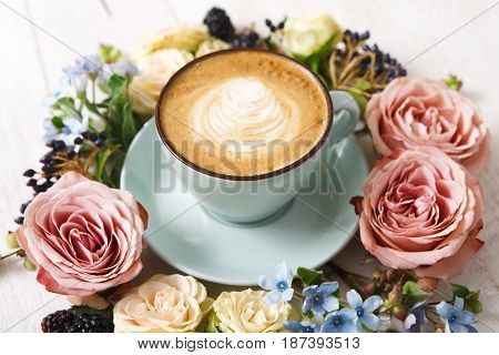 Cappuccino and flowers composition. Blue coffee cup with creamy foam, fresh and dried flowers circle at white wood background. Hot drinks, seasonal offer concept
