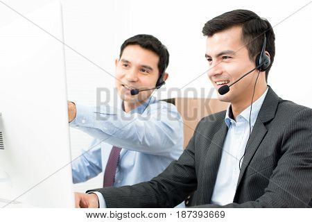 Businessmen wearing headset and looking at computer screen - telemarketing call center and customer service staff concepts