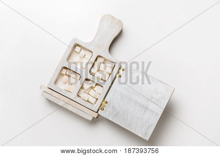 Wooden box with white sugar cubes and tongs on table, top view, white isolated background, copy space