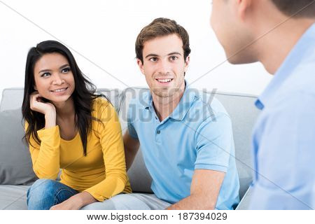 Young couple meeting with consultant (or counselor financial adviser real estate agent etc.)