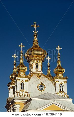 Golden domes of house church of Holy Apostles Peter and Paul of Grand Palace in Peterhof, St. Petersburg, Russia