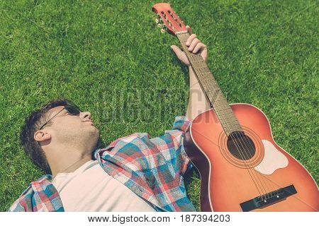 Young fashionable guy lying on grass and holding acoustic guitar. Top down point of view.