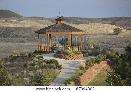 horizontal image of a beautiful gazebo with hills in the background at a public golf course in the early evening in the summer.