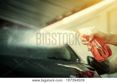 Hand holding spray bottle spraying car about to clean
