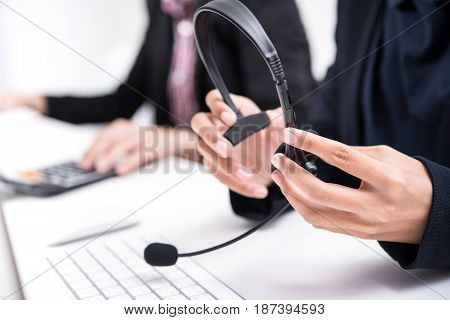 Woman hands holding microphone headset about to wear - call center telemarketer concepts