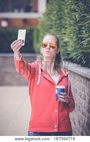 Portrait of young woman taking self portrait while enjoying her first morning coffee in paper cup.