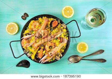 Photo of Spanish seafood paella in typical paellera, with slices of lemons, mussels and clams shells, glass of white wine, fork and spoon, and a place for text, shot from above on a teal texture