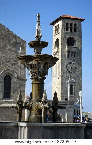 antique fountain stone building and clock tower view of the town square of Rhodes