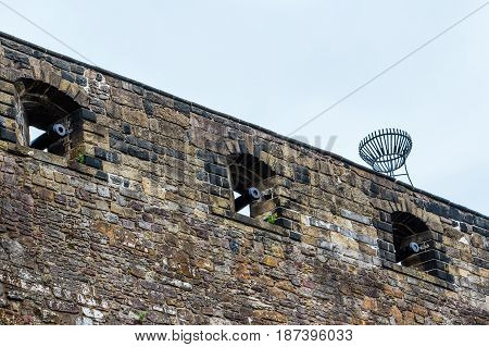 EDINBURGH SCOTLAND - SEPTEMBER 14 2014: castle fortress wall riddled with gunpowder cannon portholes atop Castle Hill at the end of the Royal Mile street.