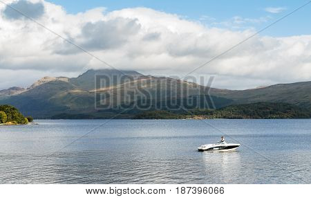 LOSS ARGYLL SCOTLAND - SEPTEMBER 27 2014: stationary speedboat with man on board floating on the calm waters of Loch Lomond with Ben Lomond mountain in the background on a sunny and bright day.