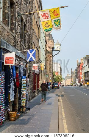 EDINBURGH SCOTLAND - SEPTEMBER 13 2014: tourist shop at the Canongate section of the Royal Mile street with the antique clock atop Canongate Tolbooth building.
