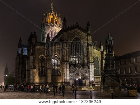 EDINBURGH SCOTLAND - SEPTEMBER 13 2014: night shot of St. Giles' Cathedral in a misty night with people and tourists passing by. This religious gothic landmark sits in the upper Royal Mile street.