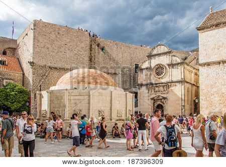 DUBROVNIK CROATIA - JULY 16th 2016: Stradun street starting square in Old Town with the Renaissance architecture of Saint Saviour church and Onofrio's Fountain beside city walls in a a sunny day.