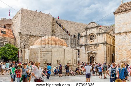 DUBROVNIK CROATIA - JULY 16th 2016: tourists roaming Stradun street starting square in Old Town with the Renaissance architecture of Saint Saviour church and Onofrio's Fountain beside city walls.