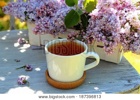 Cup of tea with a bouquet of lilacs on the old chair in the garden
