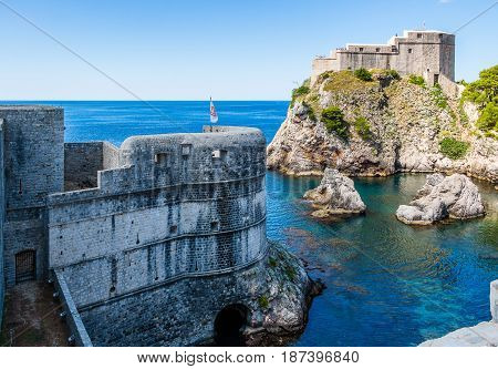 DUBROVNIK CROATIA - JULY 19th 2016: city walls and Fort Lovrijenac guarding sea cove at Old Town's Pile Gate entrance. This clear waters and rocky bay opens to a calm and blue Mediterranean sea.
