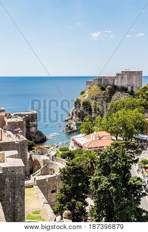 DUBROVNIK CROATIA - JULY 19th 2016: city walls and Fort Lovrijenac guarding Old Town's Pile Gate entrance. This clear waters and rocky sea cove allows for water sports practice at the Adriatic sea.