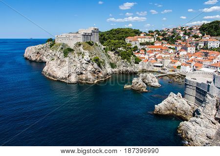DUBROVNIK CROATIA - JULY 19th 2016: sea cove and docks guarded by Pile Gate walls and Fort Lovrijenac at Old Town. Adriatic's deep blue waters attract many tourists for the sunny summer season.