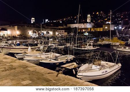 DUBROVNIK CROATIA - JULY 19 2016: nightshot of leisure boats docked at the Old Port surrounded by Old Town's illuminated stone buildings. The former Arsenal now houses a restaurant for tourists.