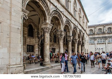 DUBROVNIK CROATIA - JULY 16th 2016: colonnade and arches in perspective at Sponza Palace front porch located at Stradun street (Placa) ending square in the Old Town.