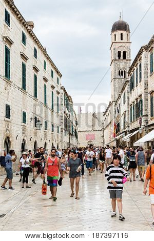 DUBROVNIK CROATIA - JULY 16th 2016: Stradun (Placa) crowded with tourists with Franciscan Church and Monastery and Pile Gate in the background in the Old Town in a cloudy summer day.