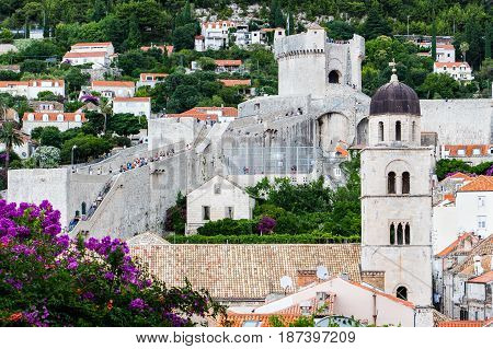 DUBROVNIK CROATIA - JULY 16 2016: Pile Gate section of Old Town city walls and Franciscan monastery tower. Tourists roam atop of the walls as they look for a different sightseeing.