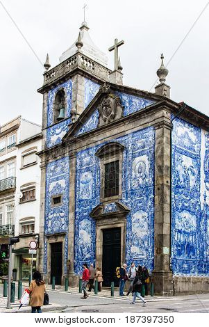 PORTO PORTUGAL - MARCH 11 2017: Chapel of Souls (Capela das Almas) church tiled facade in Rua de Santa Catarina at city old town. The painted enameled azulejos are an element of Portuguese culture.