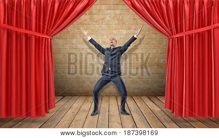 A joyful businessman standing at a wooden stage between red curtains in a victory pose. Business awards. Award winner. Best salesman.