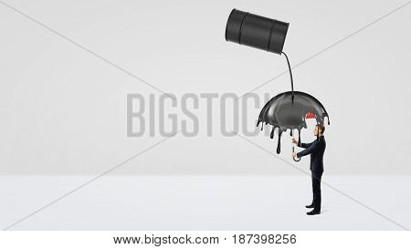 A small businessman hiding under an umbrella from crude oil leaking of a large black barrel. Oil and gas industry. Counting costs and losses. Safety and protection.