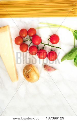 An overhead photo of basic pasta ingredients on a white marble table. Fresh cherry tomatoes, a slice of cheese, spaghetti, an onion, a garlic clove, and basil leaves, with a place for text