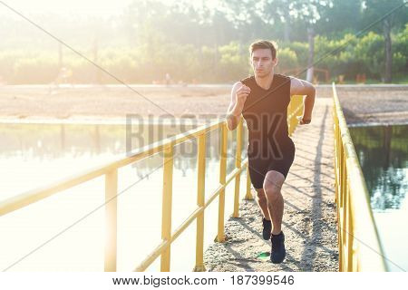 Sporty young man jogger exercising working out at morning outdoors