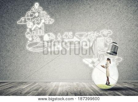 Businesswoman inside of light bulb in empty concrete room