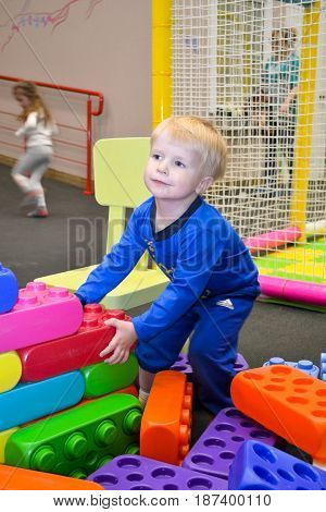 the boy in the blue suit is playing in the block constructor