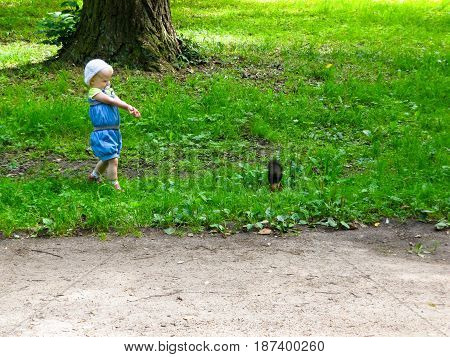 the girl in the blue suit feeding a squirrel in the woods