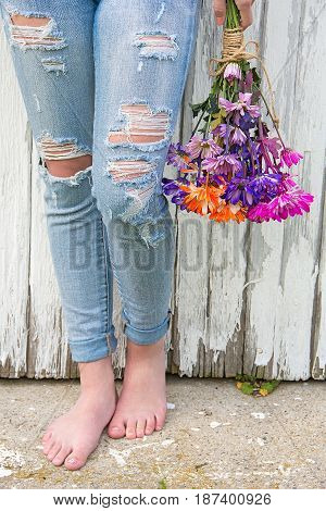 barefoot teenage girl wearing frayed blue jeans and holding colorful daisy bouquet by whitewashed barn
