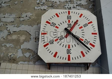 Lost city.Vintage clock.Swimming pool in abandoned city Pripyat.Chernobyl Exclusion Zone.May 19, 2017.Kiev region.Ukraine