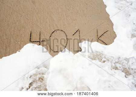 401k written in the sand with an ocean wave washing it away
