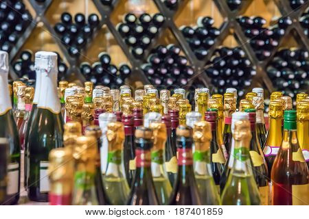 Bottle of champagne wine abstraction backdrop. Blurred alcohol bottles on shelves in supermarket. Mock up for display of product.